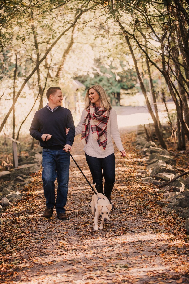 fall family photos couple walking dog in woods
