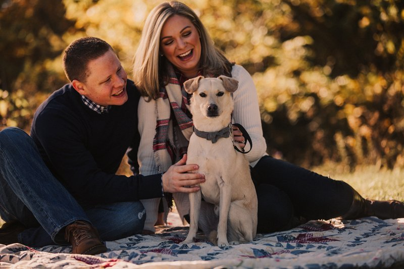fall family photos couple with dog on vintage quilt