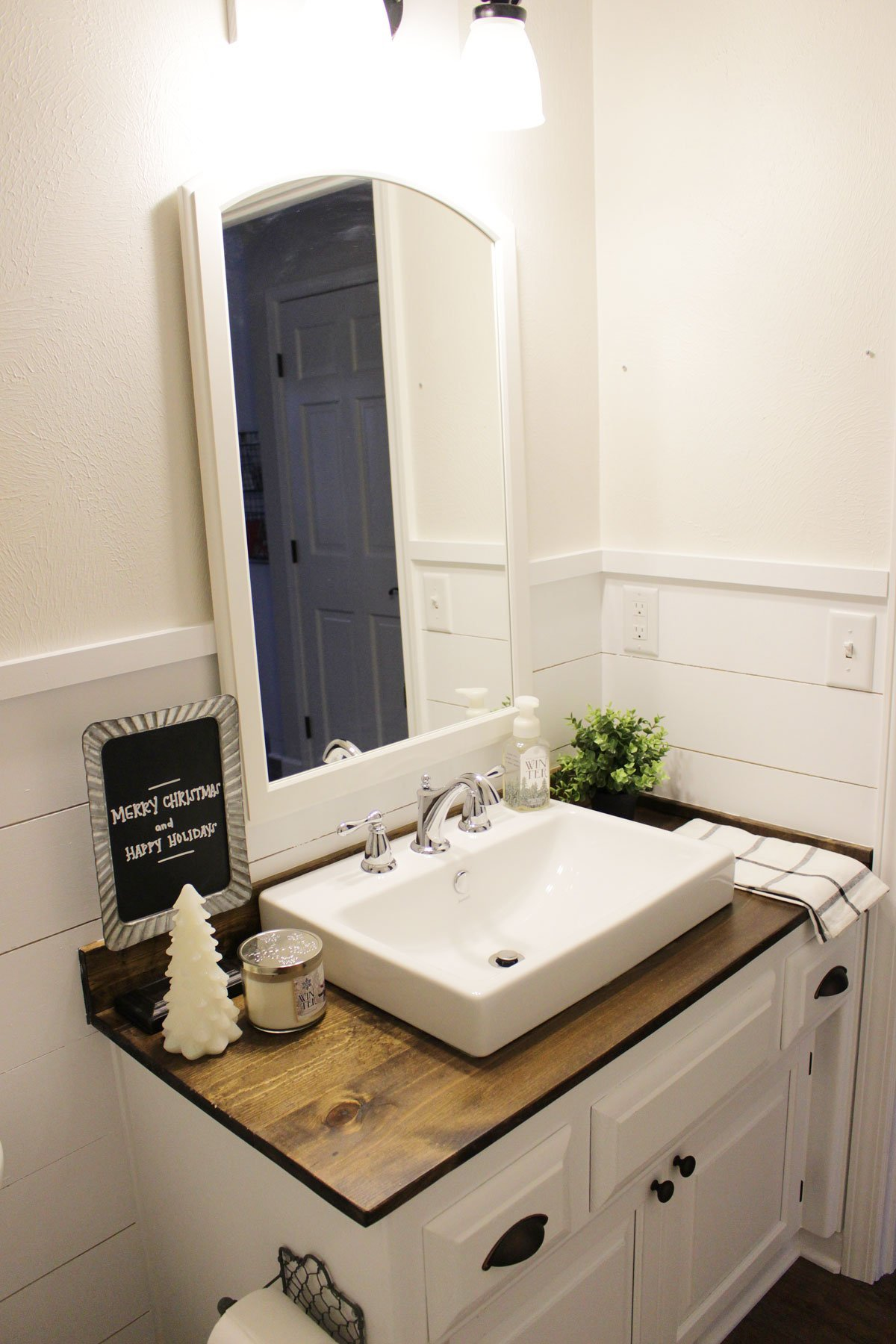 farmhouse-inspired half bathroom with shiplap and wood vanity top