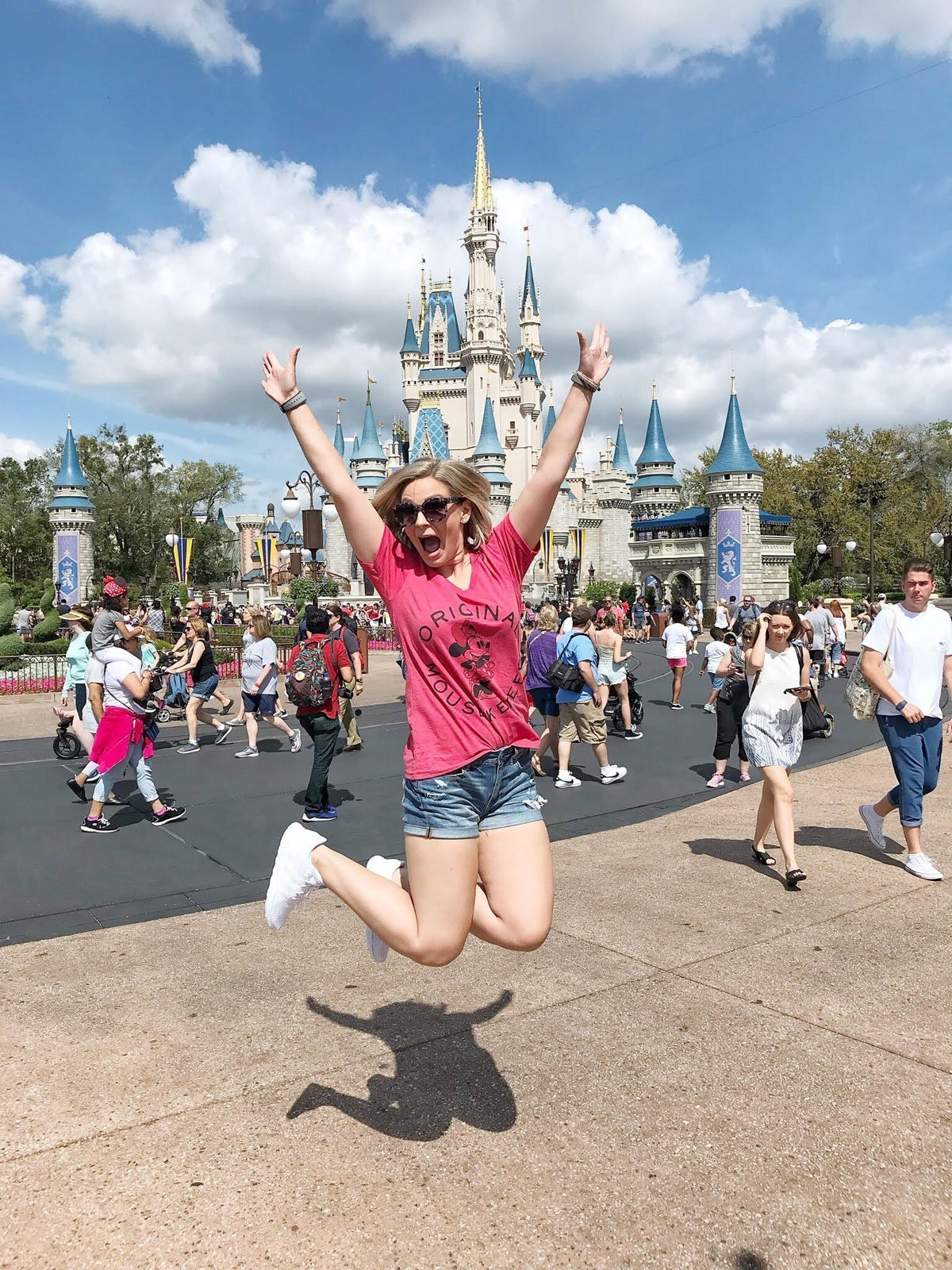 jumping in front of Cinderella's castle at Disney World Magic Kingdom